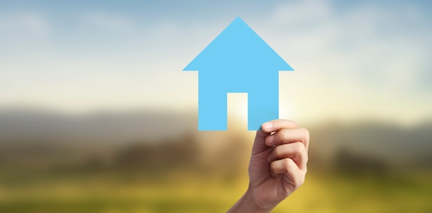 Ręce trzymając papierowy dom, dom rodzinny i ochrona koncepcji ubezpieczenia