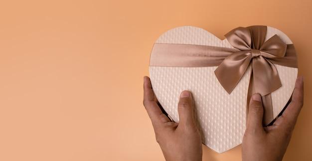 Ręce, trzymając pudełko w kształcie złotego serca