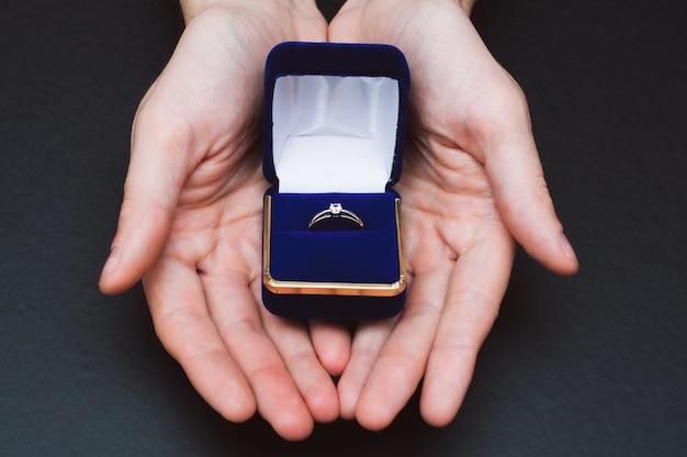 Ręce trzymając pudełko z pierścionkiem zaręczynowym