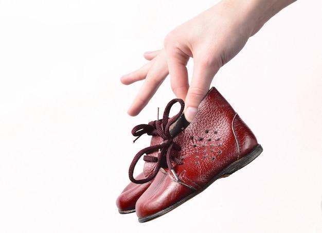 Ręce, trzymając skórzane buty dla dzieci na białym tle
