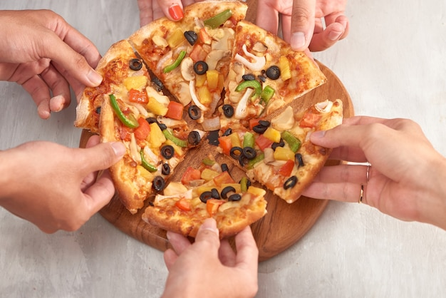 Ręce, trzymając świeżą pieczoną pizzę z topniejącego sera