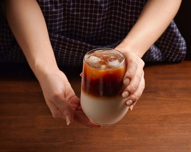 Ręce, trzymając szklankę mrożonej kawy latte. orzeźwiający letni napój składający się z dwóch warstw świeżego mleka i espresso na drewnianym stole
