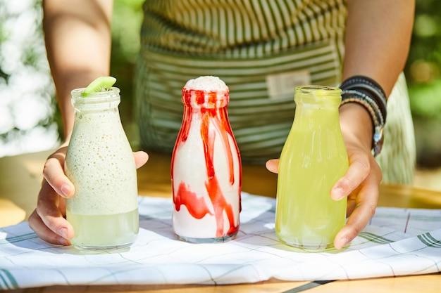 Ręce, trzymając szklankę świeżych lemoniad i koktajli mlecznych na drewnianym stole.