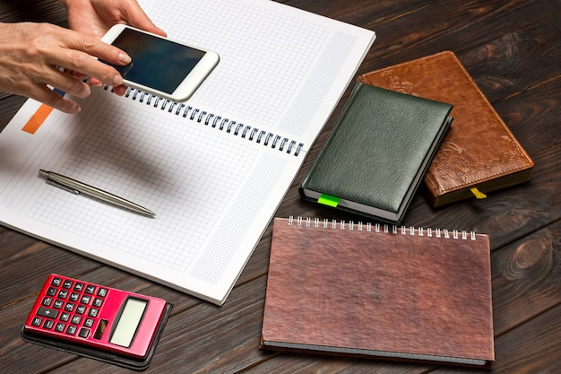 Ręce trzymając telefon komórkowy nad otwartym notatnikiem. kalkulator i zeszyty na stole
