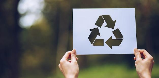 Ręce trzymając wycięty papier recyklingu pokazano