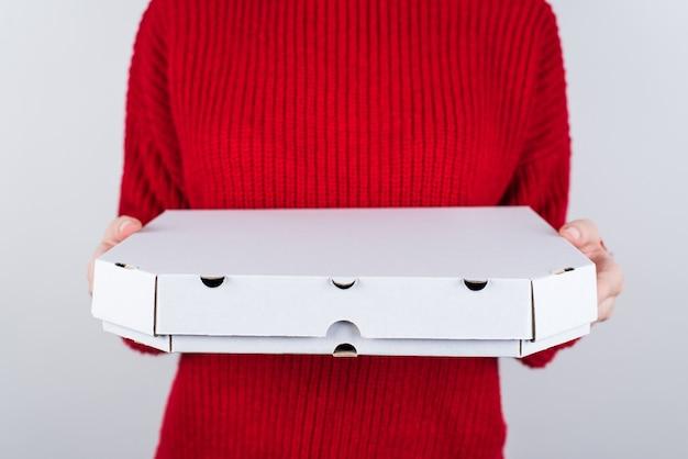 Ręce, trzymając zamknięte pudełko papierowe z pizzą w środku
