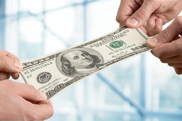 Ręce trzymające banknot stu dolarów na tle