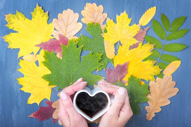Ręce trzymające biały kubek w kształcie serca z parującą kawą lub herbatą na tle jesieni opadłych suchych kolorowych liści. jesienna koncepcja bluesa.