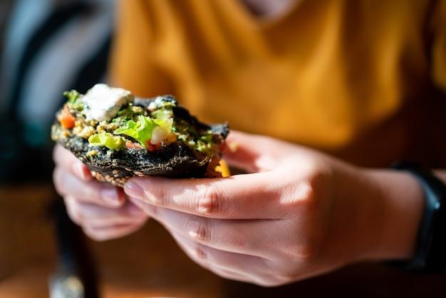 Ręce trzymające burgera z węglem drzewnym z brokułami quinoa, posypane guacamole, salsą z mango i świeżą sałatką, ugryź po przekrojeniu na pół.