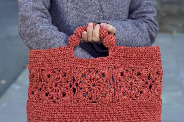 Ręce trzymające czerwoną torbę z dzianiny ciepłe ubrania i akcesoria na zimę sezonowe zakupy