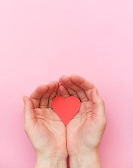 Ręce trzymające czerwone serce na różowym tle