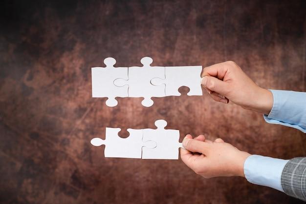 Ręce trzymające dwa kawałki układanki.współpraca w poszukiwaniu i rozwiązywaniu brakujących pomysłów w pracy.biznesmen znajdź strategię rozwiązywania, łączenia myśli