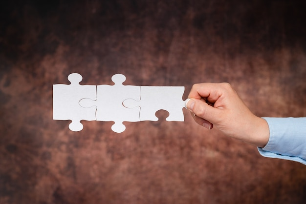 Ręce trzymające dwa kawałki układanki. współpraca w poszukiwaniu i rozwiązywaniu brakujących pomysłów w pracy. biznesmen znajdź strategię rozwiązywania, łączenia myśli