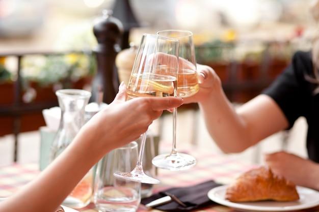 Ręce trzymające kieliszki białego wina wznoszące toast