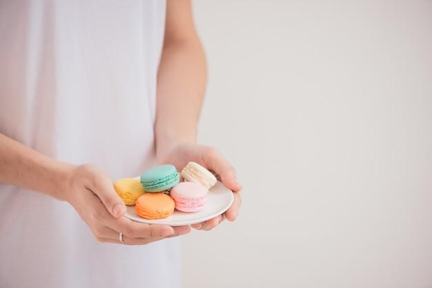 Ręce trzymające kolorowe pastelowe ciastka makaroniki lub makaroniki