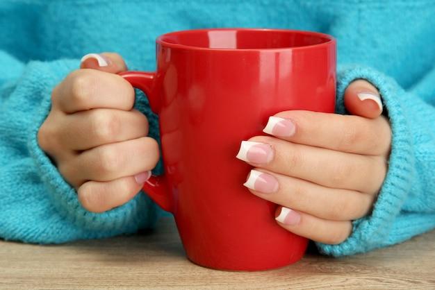 Ręce trzymające kubek gorącego napoju z bliska