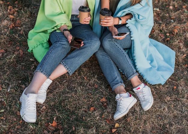 Ręce trzymające pod dużym kątem telefony i filiżanki do kawy