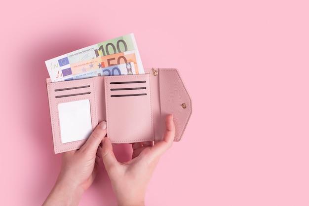 Ręce trzymające portfel z rachunkami euro wewnątrz na różowym tle
