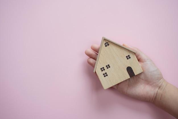 Ręce trzymające stare drewno domu na pastelowym różowym tle