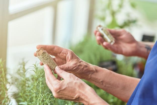 Ręce trzymające suszone pikantne zioła w maleńkiej butelce