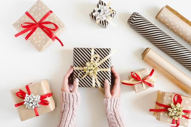 Ręce trzymające świąteczne pudełko, wiele małych pudełek zawiniętych w papier pakowy i rolki papieru