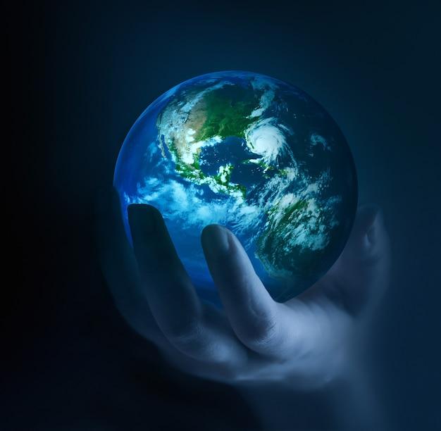 Ręce trzymające świecącą planetę w ciemności elementy tego obrazu dostarczonego przez nasa