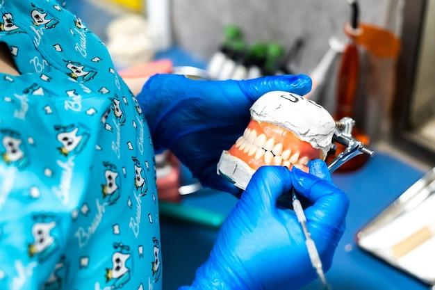 Ręce trzymające sztuczną szczękę proteza dentystyczna zęby z porcelany cyrkonowej