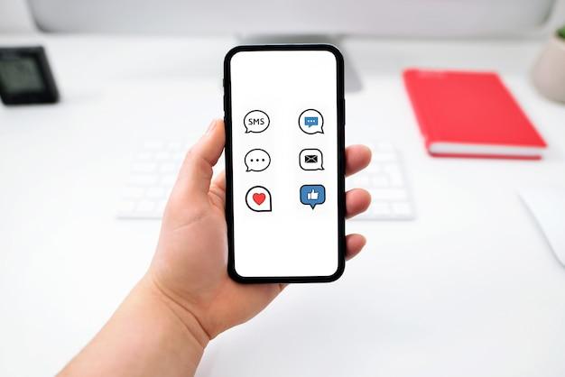 Ręce trzymające telefon z komunikatorem aplikacji na ekranie nad stołem w biurze