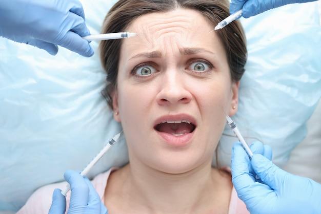 Ręce trzymające wiele strzykawek w pobliżu twarzy przestraszonej kobiety bezbolesnej kosmetologii iniekcyjnej