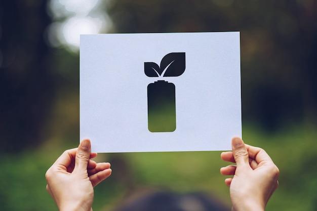 Ręce trzymające wycięty papier pozostawia baterie oszczędzające energię pokazano