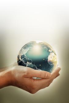 Ręce trzymające ziemię - obraz koncepcyjny dnia ziemi, oszczędzanie energii, ochrona środowiska. elementy tego obrazu dostarczone przez nasa