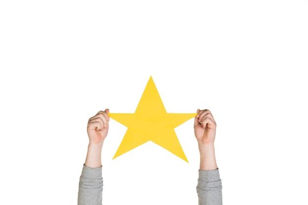 Ręce trzymające znak gwiazdy na białym tle