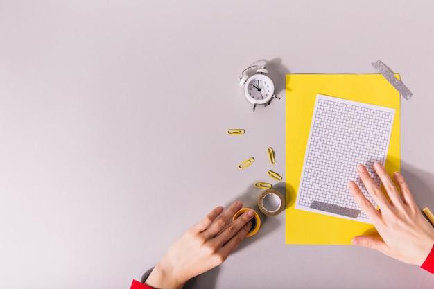 Ręce tworzące kompozycję i żółty papier oraz jasne spinacze