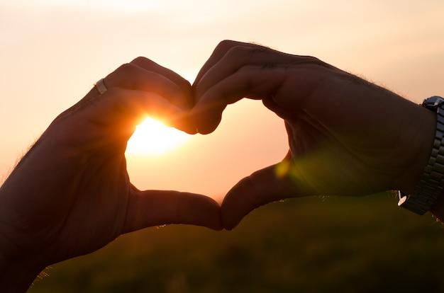 Ręce tworzące kształt serca podczas zachodu słońca