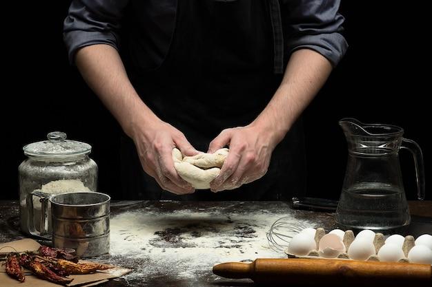 Ręce ugniatają ciasto na drewnianym stole i czarnym tle