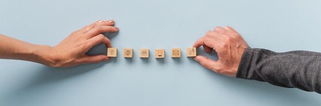 Ręce układające drewniane klocki z ikonami kontaktu i komunikacji w rzędzie.