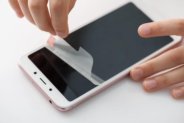 Ręce usuwające folię ochronną z ekranu smartfona