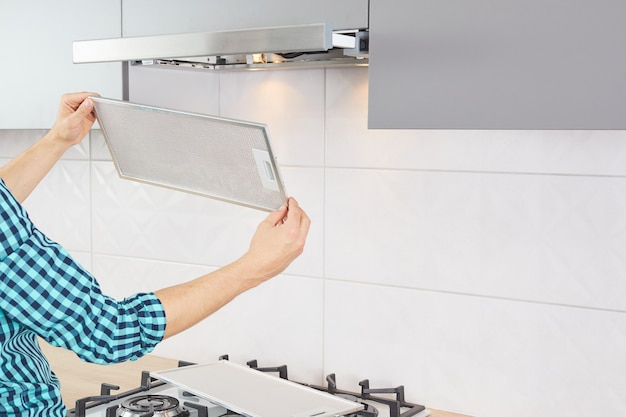 Ręce użytkownika wyjmujące filtr z okapu w celu wyczyszczenia lub serwisu. wymiana filtra w okapie kuchennym. nowoczesny wentylator kuchenny lub okap.