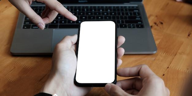 Ręce używające smartfona w biurze z pustym ekranem do makiety