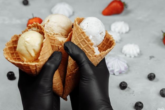Ręce w czarnych rękawiczkach ochronnych trzymają rożek waflowy z lodami. ochrona przed koronawirusem. pojęcie sprzedaży lodów podczas kwarantanny