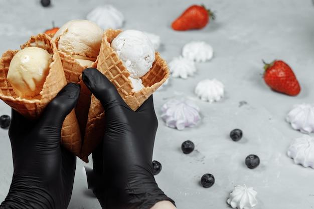 Ręce w czarnych rękawiczkach ochronnych trzymają wafel z lodami. ochrona przed koronowirusem. koncepcja sprzedaży lodów podczas kwarantanny. lody w rękach w czarnych rękawiczkach ochronnych.