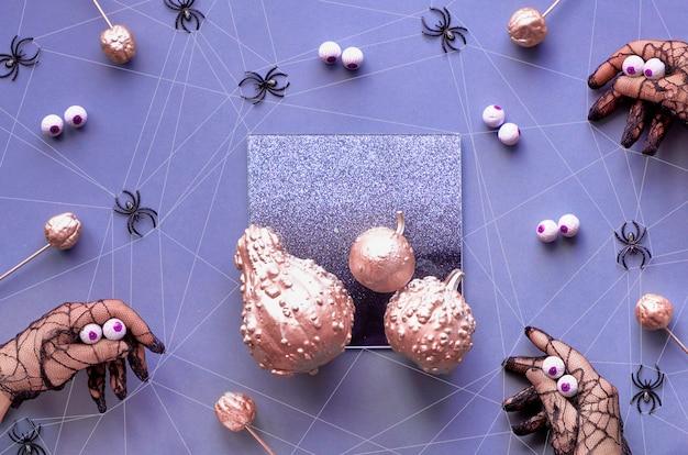 Ręce w czarnych rękawiczkach z siatki imitujących duże pająki o czekoladowych oczach. kreatywne upiorne mieszkanie halloween leżało w fioletowym, metalicznym różu i czerni z dyniami i pająkami.