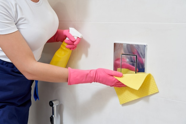 Ręce w gumowych rękawicach ochronnych przycisk spłukiwania toalety. koncepcja dezynfekcji