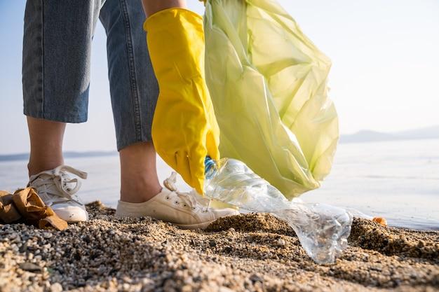 Ręce w gumowych rękawiczkach z workiem na śmieci sprzątają śmieci na jeziorze. oczyszczanie brzegu jeziora z bliska. świadomy stosunek do środowiska.