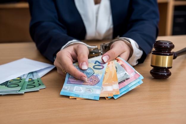 Ręce w kajdankach aresztowany za łapówkę w postaci banknotów euro