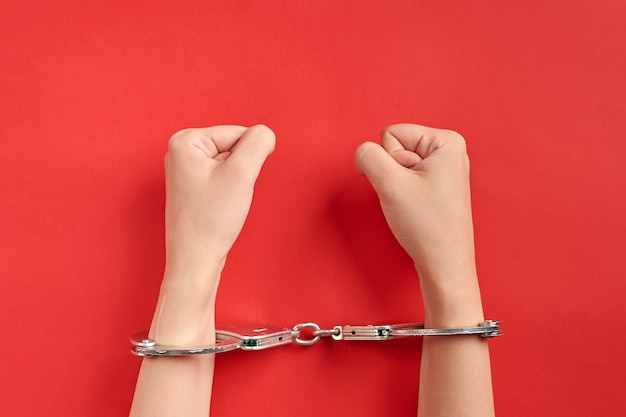 Ręce w kajdankach na czerwonym tle. koncepcja więzienia. pozbawienie wolności i pojmanie sprawców. pięści.