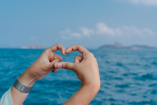 Ręce w kształcie serca na tle morza. ręce tworzące kształt serca.