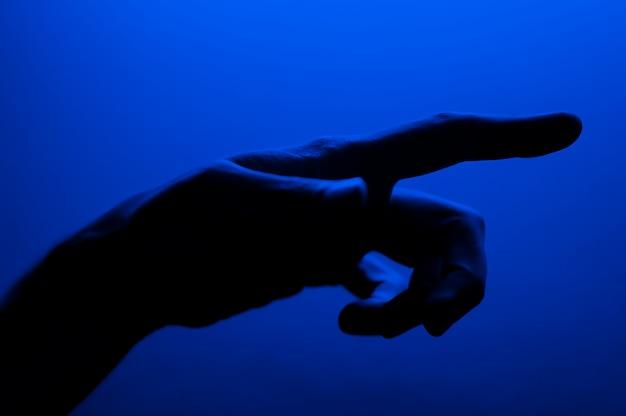 Ręce w neonowym niebieskim kontraście neonowym świetle. mężczyzna seansu ręki gesta palmowy znak. fotografia artystyczna.