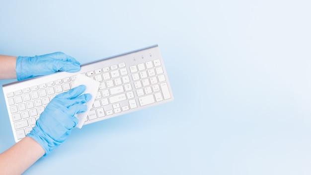 Ręce w niebieskich rękawiczkach medycznych do czyszczenia klawiatury środkiem dezynfekującym