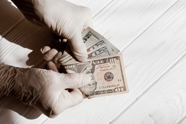 Ręce w rękawicach ochronnych i dolarów